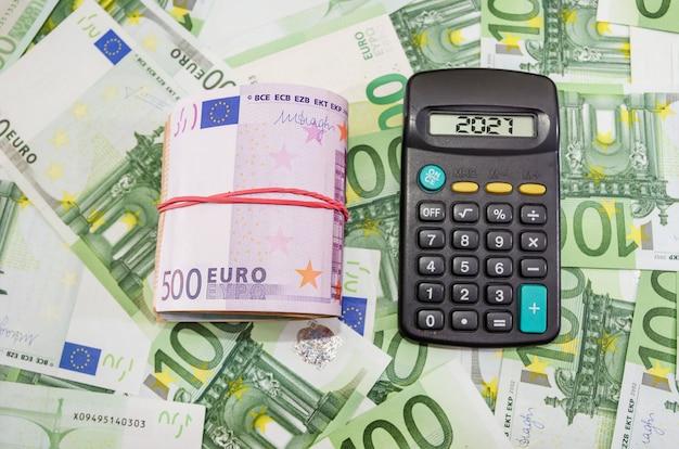 Gevouwen eurobankbiljetten en rekenmachine op geld. eurobankbiljetten gebonden met elastische band. financieel concept.
