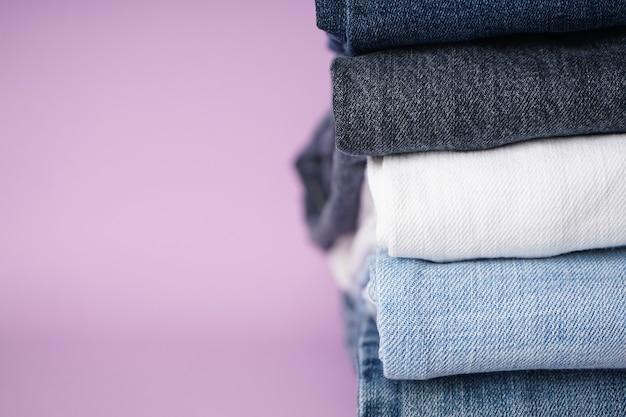 Gevouwen geassorteerde jeans op paarse achtergrond, ruimte voor tekst.