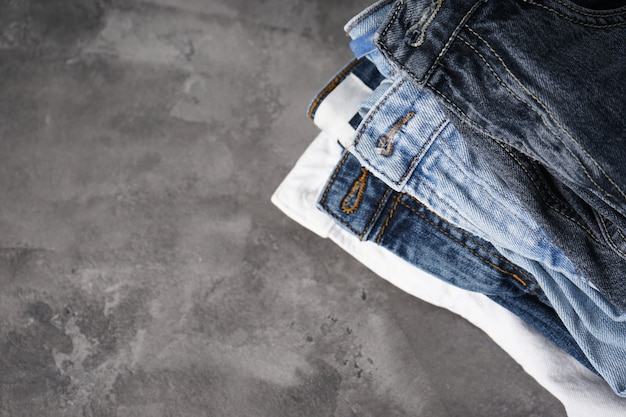 Gevouwen jeans op grijze achtergrond met plaats voor tekst. plat leggen.