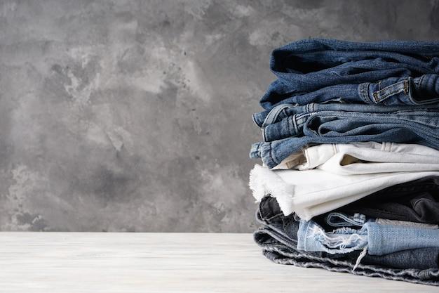 Gevouwen jeans op grijze achtergrond met ruimte voor tekst.