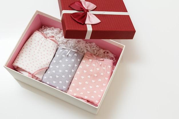 Gevouwen katoenen slipje van verschillende kleuren in een doos en op het witte oppervlak