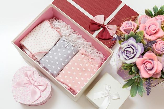 Gevouwen katoenen slipje van verschillende kleuren in een doos met kunstbloemen op het witte oppervlak