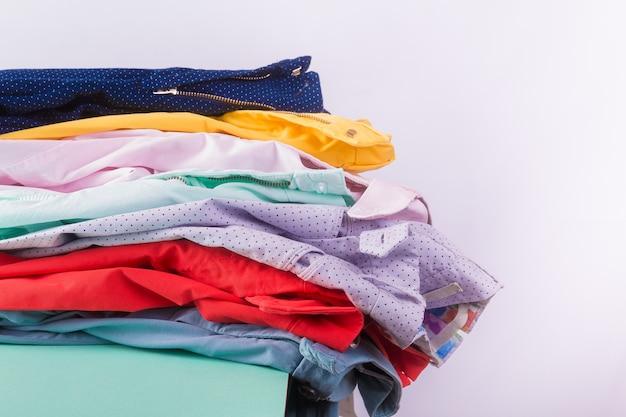 Gevouwen kleurrijke broeken en jeans. stapel heldere vrouwelijke broeken. detailopname.