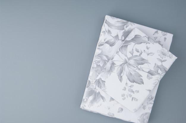 Gevouwen nieuw beddengoed met patronen op grijze achtergrond, bovenaanzicht
