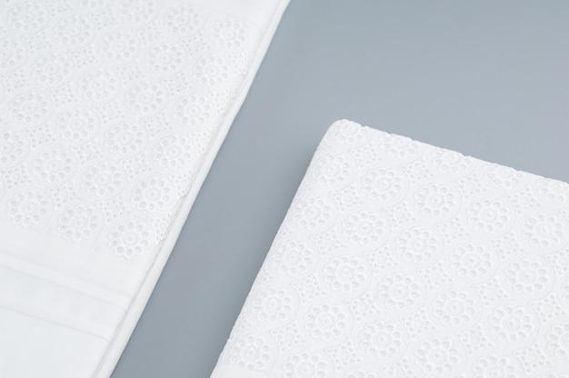 Gevouwen nieuw tafelkleed met geborduurde patronen op een grijze achtergrond, bovenaanzicht