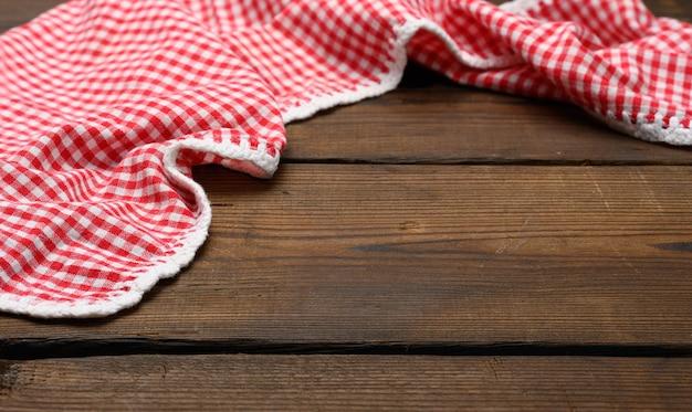 Gevouwen rood en wit katoenen keukenservet op een houten bruine achtergrond, bovenaanzicht, kopieerruimte
