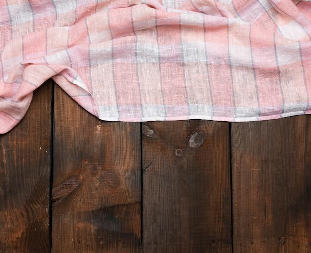 Gevouwen roze witte keukenhanddoek op bruine houten achtergrond, bovenaanzicht, kopie ruimte