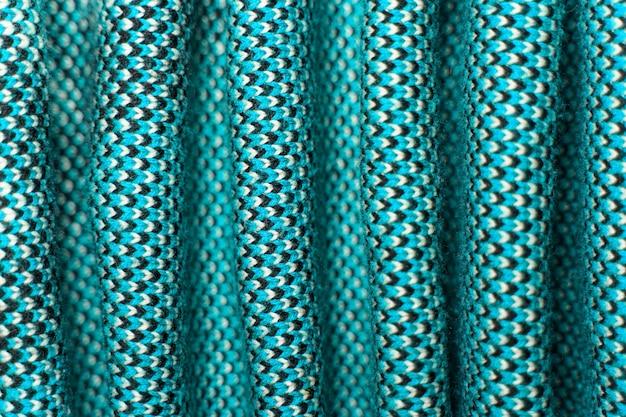 Gevouwen synthetische gebreide stof met patroonelementen van blauwe, zwarte en witte garens van dichtbij.