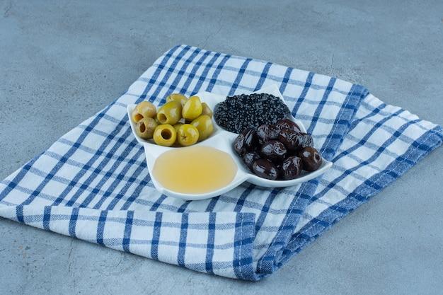 Gevouwen tafelkleed onder een schaal met pitloze olijven, honing en kaviaar op marmer.