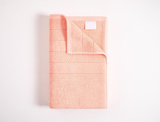 Gevouwen zachte koraal badstof handdoek met witte lege label tegen een witte achtergrond