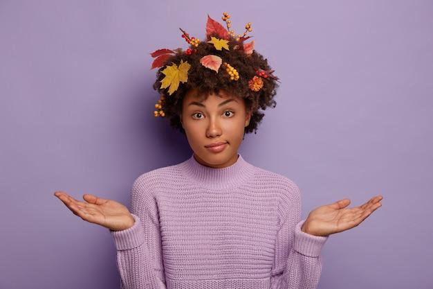 Gevraagde clueless vrouw spreidt palmen, heeft herfst rijpe planten in het kapsel, draagt een gebreide trui, kijkt niet op de hoogte van de camera, geïsoleerd op paarse achtergrond.