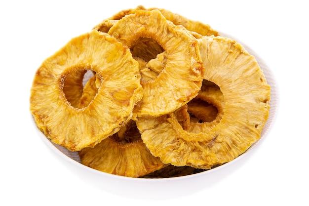Gevriesdroogde ananasringen in een witte schotelclose-upgeïsoleerde voedselproducten