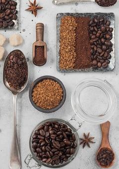 Gevriesdroogde instant koffie korrels met gemalen koffie en bonen in stalen plaat met glazen pot en verschillende lepels en scoops op witte achtergrond.
