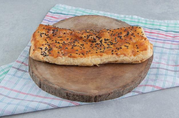 Gevuld gebakje met sesamzaden op houten stuk.