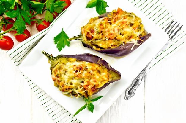 Gevulde aubergines met gerookte borst, tomaten, uien, wortelen met knoflook, kaas en kruiden in een bord op een servet op houten plank achtergrond van bovenaf