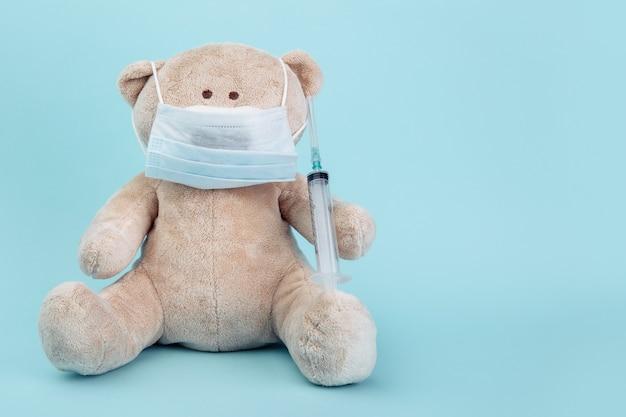 Gevulde beer dier in masker met spuit geïsoleerd op blauw. kinderarts concept