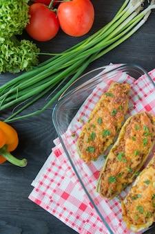 Gevulde courgette met gehakt en geraspte kaas in een glazen bakplaat. donkere houten achtergrond. gezond evenwichtsvoedsel. het koken van voedsel.