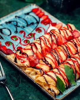 Gevulde crêpe gegarneerd met aardbeien- en chocoladesiropen
