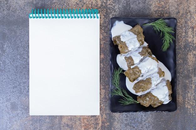 Gevulde druivenbladeren dolma op plaat met yoghurt en notitieboekje.