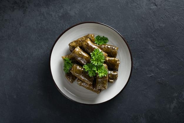 Gevulde druivenbladeren met rijst en vlees op een donkere achtergrond