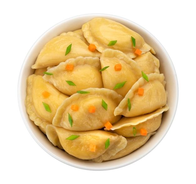 Gevulde dumplings, eigengemaakte russische vareniki, dumplings in kom geïsoleerd op een witte achtergrond, bovenaanzicht