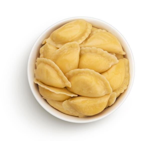 Gevulde dumplings, eigengemaakte russische vareniki, pelmeni in kom die op wit wordt geïsoleerd