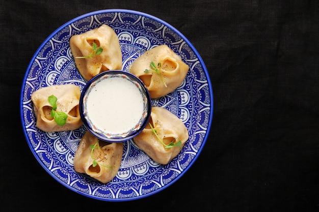 Gevulde dumplings, manti van deeg en gehakt, close-up traditionele chinese dim sum dumplings op donkere tafel