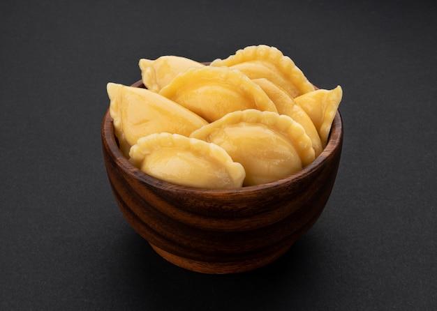 Gevulde dumplings, zelfgemaakte russische vareniki, pelmeni in houten kom op zwart