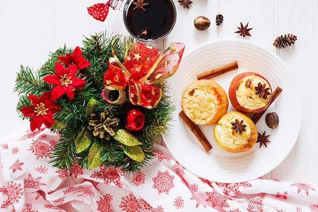 Gevulde gebakken appels met kwark, rozijnen en amandelen voor kerstmis op een witte tafel. xmas eten dessert.