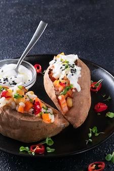 Gevulde geroosterde zoete aardappel of yam met kikkererwten, rijst, groenten, rode chili peper en yoghurt saus dressing