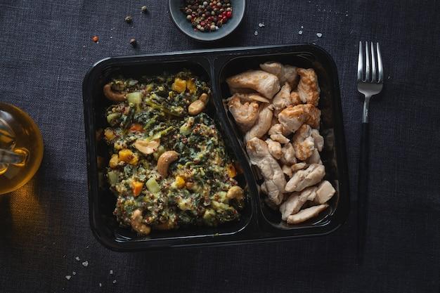 Gevulde groene boerenkoolsalade met cashew en gekookte kipfilet geserveerd in lunchbox. gezonde levensstijl.