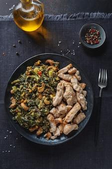 Gevulde groene boerenkoolsalade met cashew en gekookte kipfilet geserveerd op donkere plaat. gezonde levensstijl.