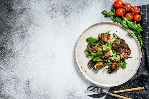 Gevulde kipfilets, filets gerold in spek met groene salade. grijze achtergrond