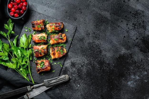 Gevulde kipfilets, filets gerold in spek. zwarte achtergrond