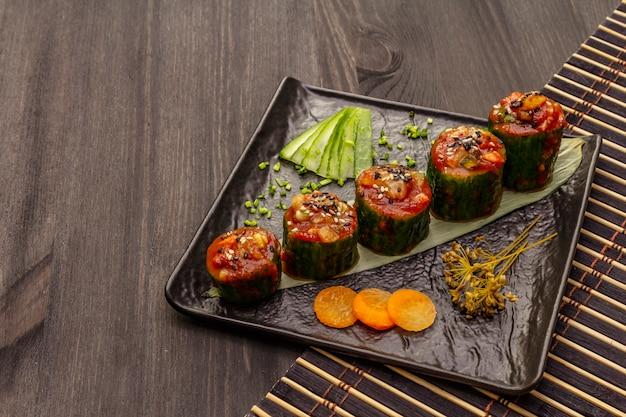 Gevulde komkommers in koreaanse stijl. kojori kimchi pittige snack. gefermenteerde en gemarineerde groenten. houten achtergrond