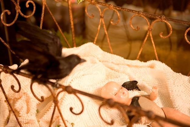 Gevulde merel en babypop in antieke wieg