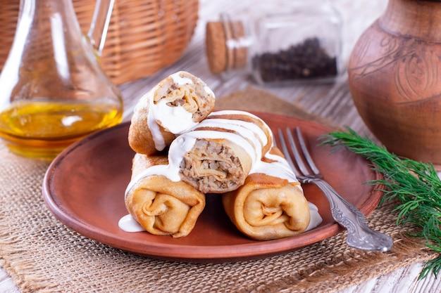 Gevulde pannenkoeken-pannenkoeken met vlees en saus in een keramische plaat op tafel