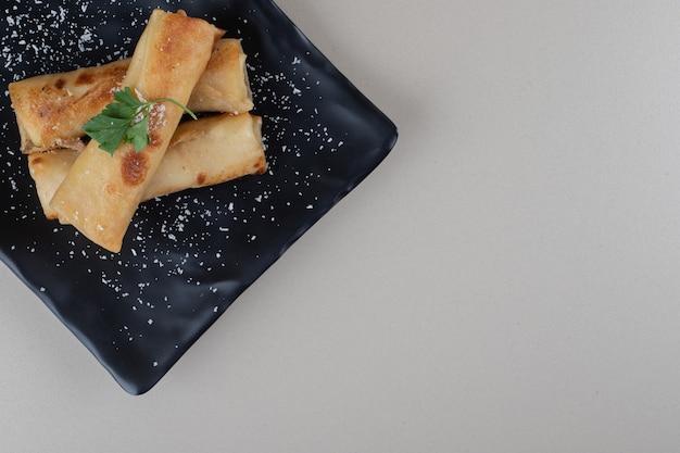 Gevulde pannenkoekverpakkingen op een zwarte schotel op marmeren achtergrond.