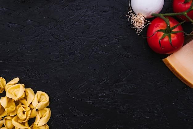 Gevulde pasta in de buurt van groenten en kaas