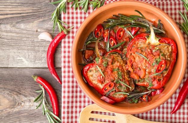 Gevulde rode paprika met pikante tomatensaus en rozemarijn in kleischotel bij rustieke houten