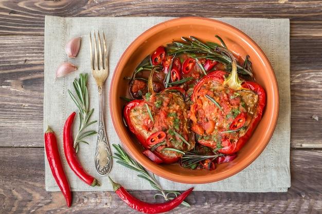 Gevulde rode paprika met pikante tomatensaus en rozemarijn in kleischotel op het rustieke houten oppervlak.