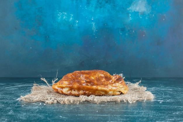 Gevulde taart met jute op marmeren tafel.