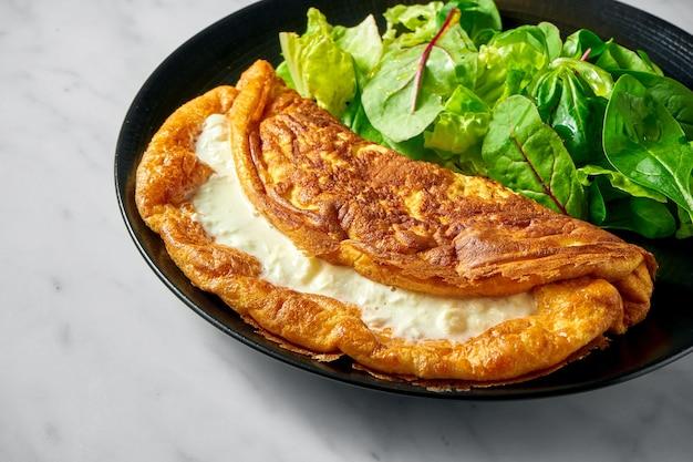 Gevulde weelderige romige omelet met slamix in zwarte plaat op wit marmer