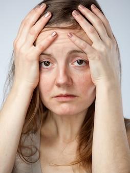Gewanhoopte vrouw, handen op het voorhoofd