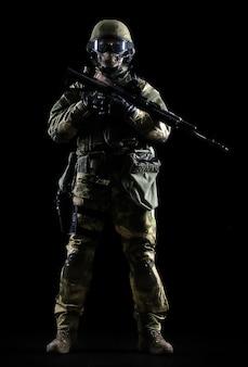 Gewapende man in camouflage staat met een pistool in zijn hand. gemengde media