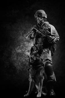 Gewapende soldaat van een speciale eenheid met een machinegeweer staat met zijn herder. gemengde media