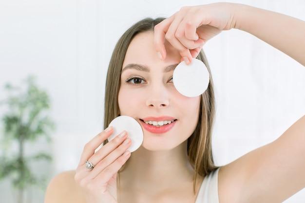 Gewas aantrekkelijk jong vrouwelijk reinigend gezicht met katoenen stootkussens op een lichte achtergrond in studio. schoonheidsconcept, huidverzorging en huidproblemen