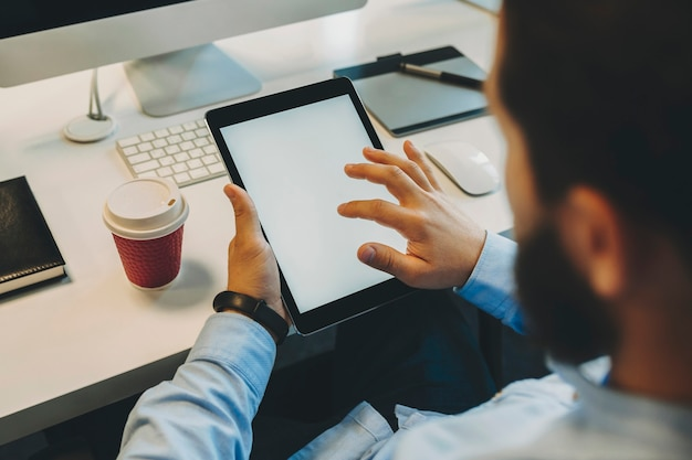 Gewas achteraanzicht van bebaarde man in blauw shirt scherm van tablet in handen aan tafel met computer en papieren beker met drank aan te raken
