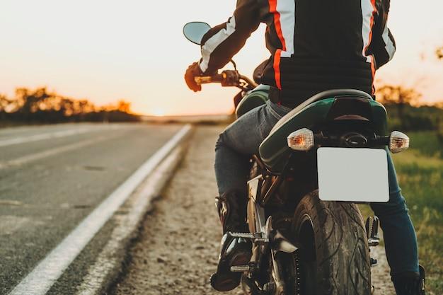 Gewas achteraanzicht van mannelijke ruiter in beschermende laarzen en jas verplaatsen op snelweg van langs de weg op backlit onscherpe achtergrond van lege route