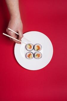 Gewas die sushi op rode achtergrond met de hand plukken